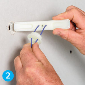 Assemble your GeeFix wall anchor system as shown above by threading the supplied blue pullcord through the round wall plug, the curved back plate, and back through the wall plug.
